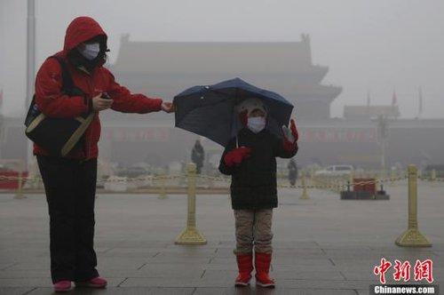 """1月31日清晨,北京降水相态多样,雨夹雪、雪、冻雨同时存在,新年以来第四次""""雾霾压城""""持续至第五日。受冷空气影响,当日北京大部分地区的空气质量指数转为重度污染级别,2月1日有望连跳二三级,达到优良级别。图为游客在雾气重重的北京天安门广场游玩。中新社发 刘关关 摄"""