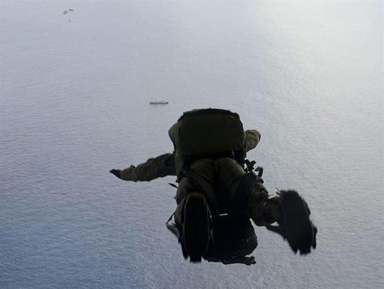 图为美国空军第48救援中队的空降救援人员从C-130上跳出瞬间,画面中间的黑色物体就是遇险的渔船。