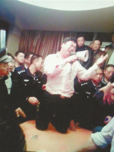 4月19日,泰州市滨江工业园区管委会招待中心,一男子跪在酒桌上喊话求饶。李根 摄