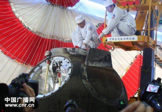 工作人员进入返回舱,取出舱内物品(中广网记者刘梦 摄)