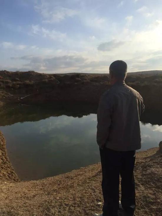 2015年10月22日,内蒙古鄂尔多斯市中和西镇蓿亥图牧业村,牧民拉外站在储水坑旁,由于附近河流已经干涸,水坑里的水也快不够用了。新华社记者吴锺昊