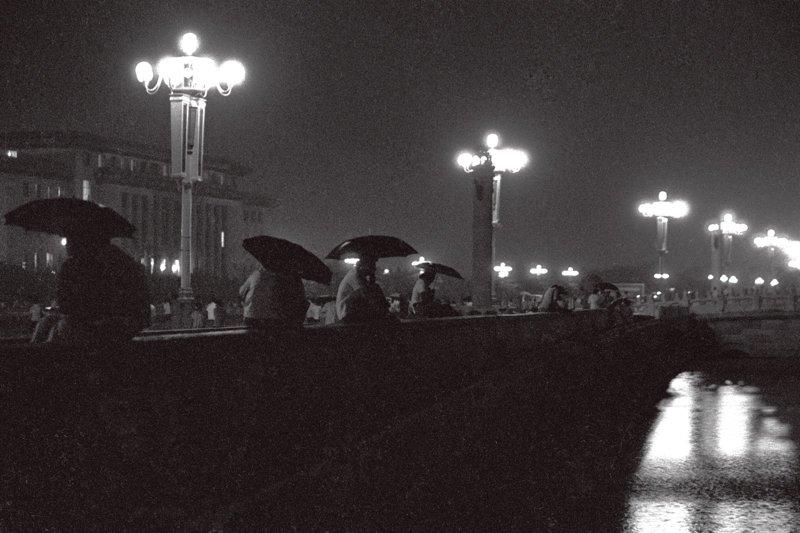 20世纪70年代末期,晚上在广场谈恋爱的年轻人。小雨中,恋人们撑着伞偎依在一起。