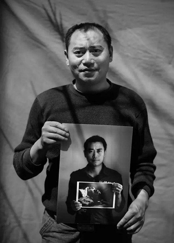 """2014年5月4日,四川省安县雎水镇。""""汶川地震""""6周年,地震幸存者35岁的李德强拿着地震1周年时拍摄的肖像,流下了眼泪。"""
