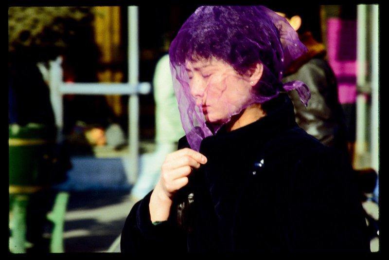 20世纪80年代,北京在春秋季节常会有沙尘暴。图为一位女士系着纱巾防尘。