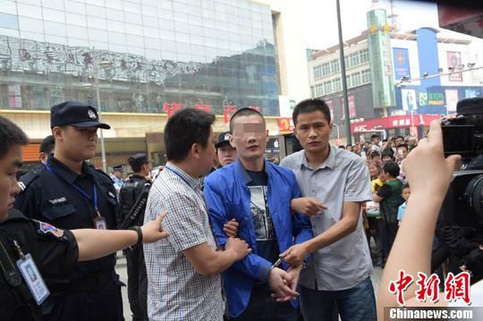 24日上午,嫌犯在警方押解下指认现场。 图片为警方提供 摄