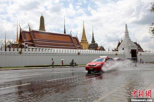当时10月29日,湄南河水位继续上涨,泰国湾的高海潮水又奔袭而至,洪水越过湄南河防洪堤进至曼谷著名景点玉佛寺。图为当日中午进袭寺前的洪水已呈强弩之末,但有车驶过仍激起阵阵浪花。中新社发 余显伦 摄