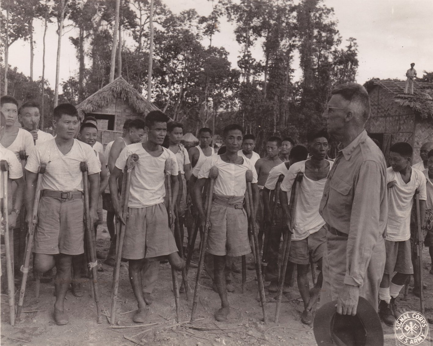史迪威将军脱帽对着一群年轻的中国退伍军人讲话。战争致残的军人回到平民生活之前,先在这里学习新的生存技能――铁艺、编织、木工活等。这个营地此时由中美共同管理经营,大约有两百多名不同程度伤残的退伍士兵。伯克林中士拍摄于利多公路的康复营地,1944年7月15日。