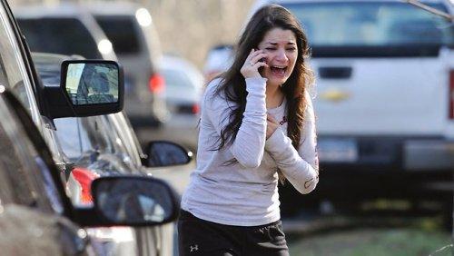 图为一名女性在桑迪·胡克小学外打电话等待其亲人的消息。