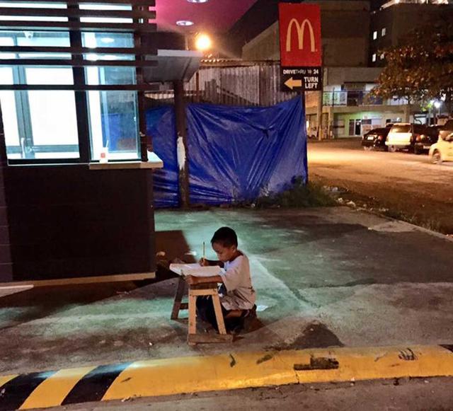 菲小女孩坐垃圾油罐上写作业