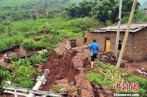 图为损毁的民房及电力设施彭洪摄