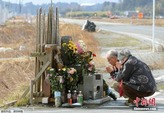 图为福岛核电站附近的namie镇,当地居民为遇难者祈祷.