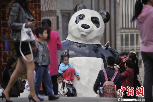 重庆街头现巨型熊猫雕塑 吸引小孩合影(图)
