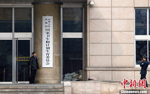 """3月17日上午11时许,原卫生部大楼挂上了""""国家卫生和计划生育委员会""""的新牌子。图为保安为一名工作人员和新牌合影。中新社发 张浩 摄"""