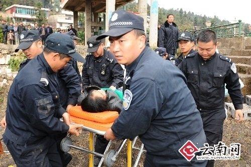 民警抬着晕倒妇女快速赶往医疗点