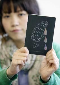 图为日本京都市某企划公司推出的《失恋疗伤手册》,手持手册的是参与制作的企划人员藤田珠美