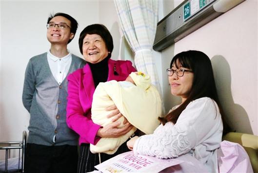 卢光琇(中)怀抱着试管婴儿罗优群(左)夫妇的女儿