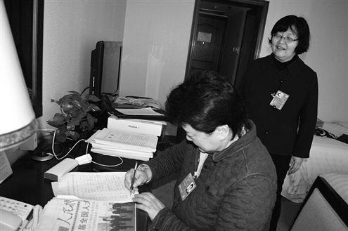 有代表来找赵冬苓(站立者)为议案签名。