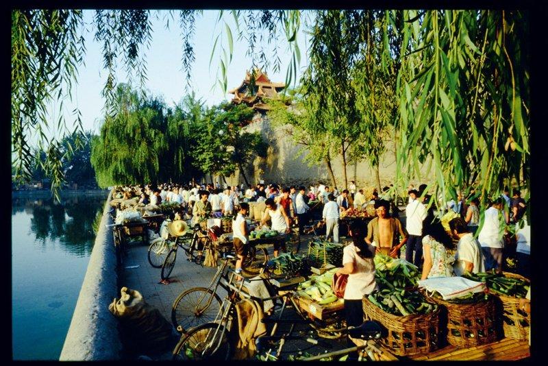 早市是京城百姓生活的一大特色。20世纪80年代初期,早市开始逐渐活跃起来。早市起初是为解决市民购买蔬菜水果方便,以及安置个体就业而设,后来逐渐扩大到售卖各种日用百货。早市一般设在皇城根附近或人口密集的街区,自天蒙蒙亮就开始,一直到中午前闭市。图为清晨,小贩们蹬三轮车载着新鲜的蔬菜到早市出售,早市背靠紫禁城,面对筒子河,老北京的生活情趣尽显无余。