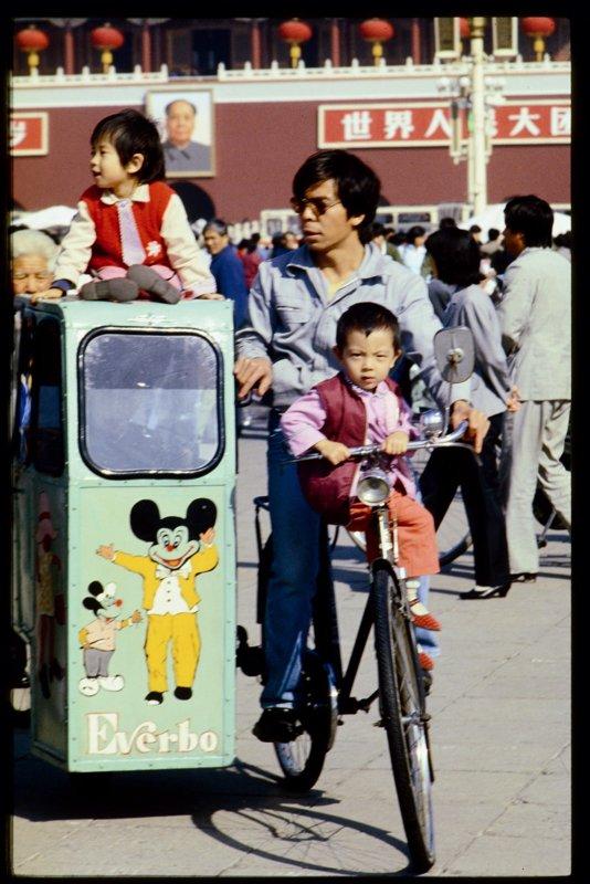 """北京城在翁乃强的镜头中就是聚光灯照射下的一个大舞台,同一个地点、跨越了30年的影像,观看之后给人强烈的震撼――从手举""""红宝书""""的游行人群到青年们的翩翩起舞;从雨夜在广场谈恋爱的青年男女到换房大会。无论历史如何激荡,都有一个身影,举着照相机在旁观记录着眼前的一切。图为20世纪80年代初,在广场上游玩的父子。"""