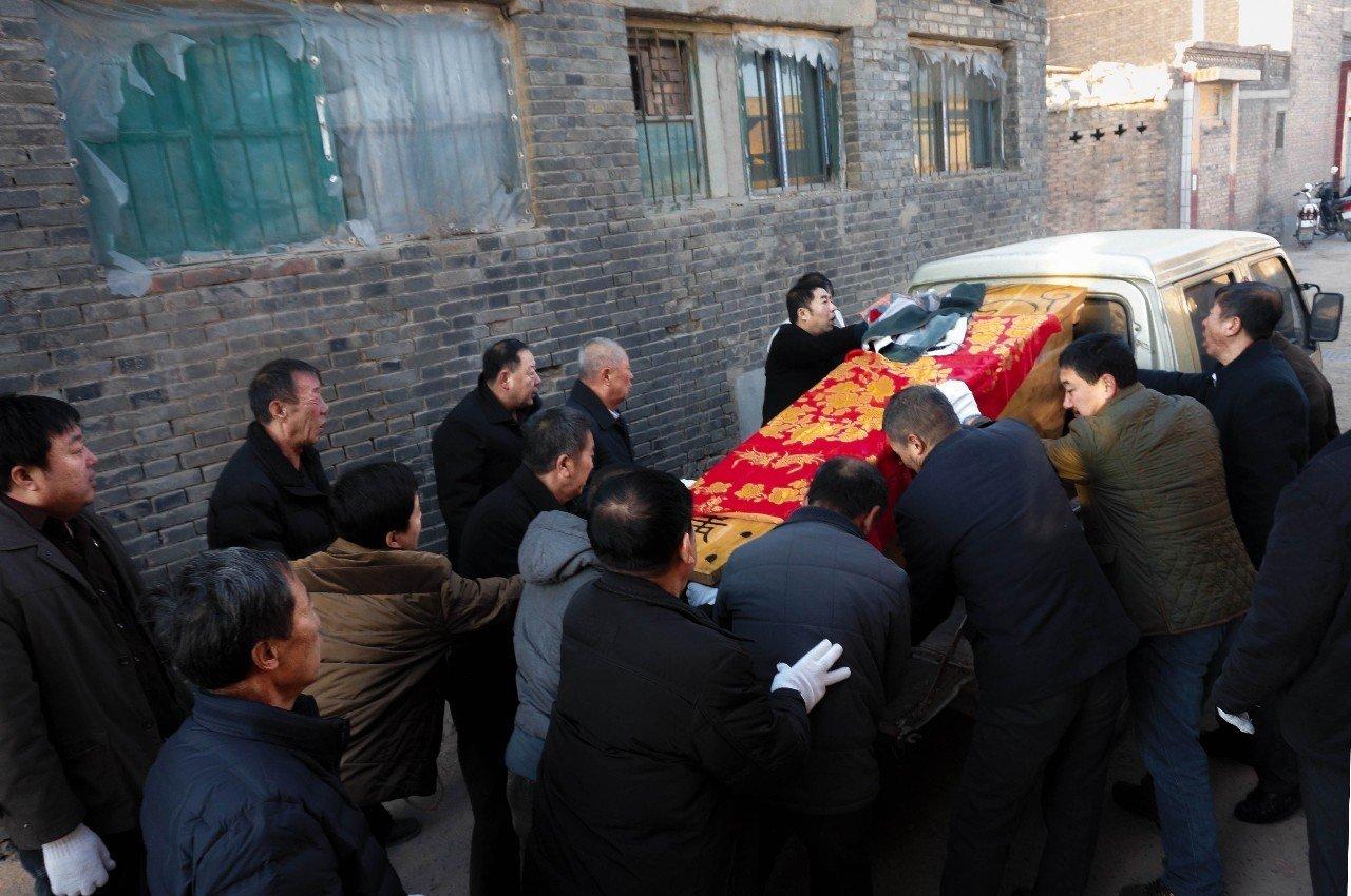 第二天早上,队里的乡亲们帮忙把准备好的实木棺材抬到车上,到医院接死者的遗体去灵堂。