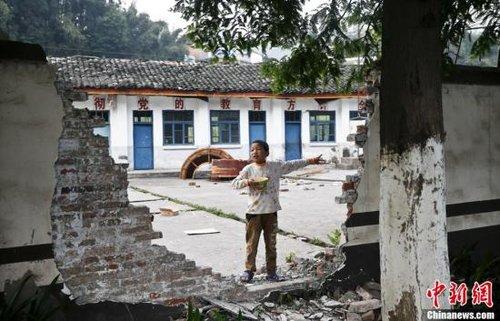 4月25日,9岁的鲁小杰站在芦山朝阳村中心小学的断墙前,他还端着自己的早饭方便面。由于家就在附近,他常来学校转转,他的哥哥甚至把帐篷搭在了学校里。地震时是周六,学生并没在这里,因而避免了人员伤亡。鲁小杰说,自己很想和同学们在一起,但还得等待板房小学的建成。中新社发 张浩 摄