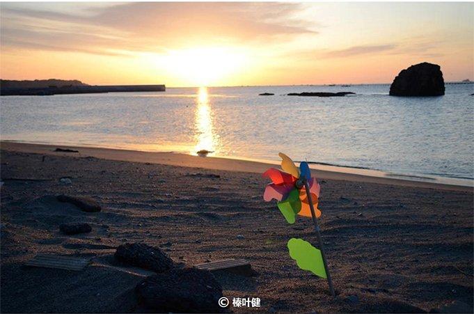 """""""3・11""""地震两年后灾区海边的日出。在日本东北地区,人们会为早夭的婴儿准备风车,作为他们在另一个世界的玩具。"""