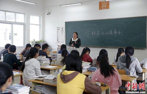 """4月26日上午8点半,宝兴中学高三(二)班开始上第一节课,黑板上老师写着""""学习是最好的安慰剂""""。中新社发 张浩 摄"""