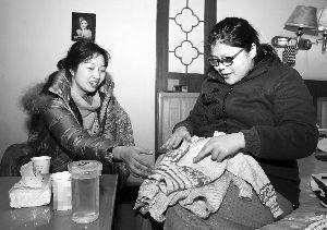 工作人员为乐燕(右)即将出生的孩子准备了小毛衣