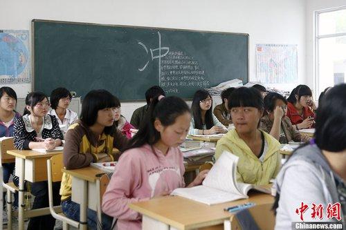 """4月26日上午8点半,宝兴中学高三(二)班开始上第一节课,教室的黑板上写着大大的""""冲""""。中新社发 张浩 摄"""