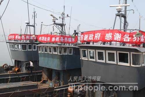 """3艘平安返回的渔船上挂出""""感谢政府感谢各级媒体""""的横幅。"""