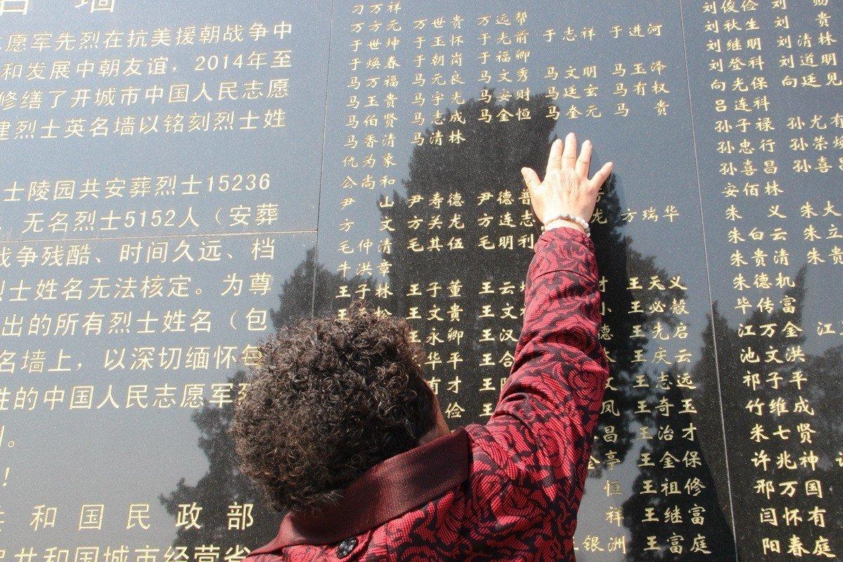 志愿军烈士马魁元的女儿马秀兰抚摸写有父亲名字的英烈墙。
