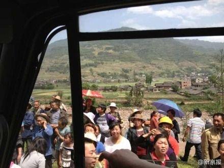 四川雅安芦山民众自发向救援车中扔食物和水