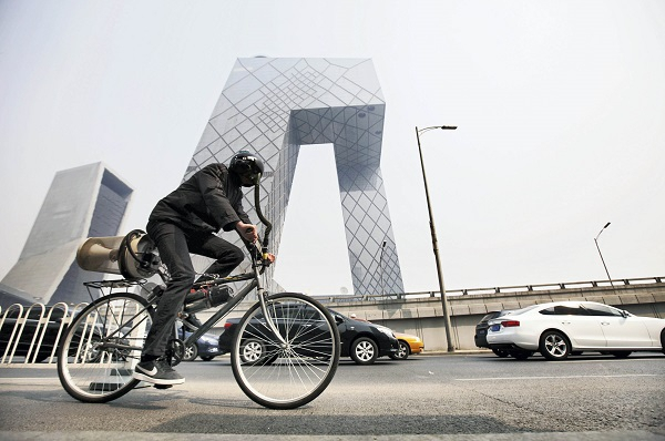 """2013年3月26日,英国艺术家马特・霍普骑着自己发明的""""空气过滤单车""""穿行在雾霾笼罩的北京街头"""
