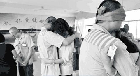 """2009年6月12日,河南省许昌监狱囚犯的眼睛被蒙上了红丝带对妻子说着情话,盼监狱重设""""夫妻房"""""""