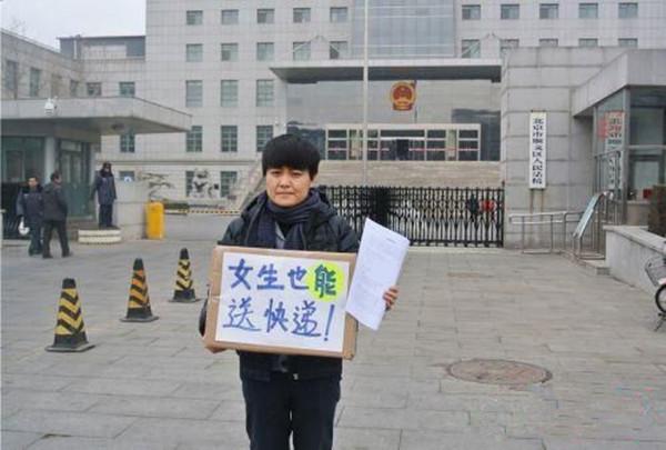 """小卢在顺义区法院门前举着""""女生也能送快递""""的牌子"""