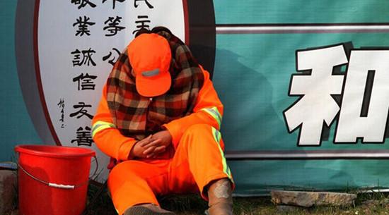 每天必须12小时在路面值守以时刻保持路面的清洁,环卫工人只能蜷缩在马路啃馒头、打瞌睡