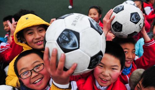 学生们抱着足球去做操(资料图)