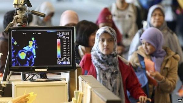 韩国出入境机构在对来自感染地区的人进行发热检测
