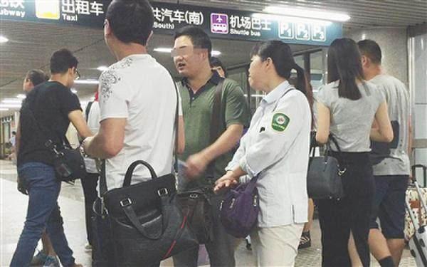 """北京西站A1出口,一名女医托身着带有""""北京公交集团""""字样的衣服,与两名同伙聊天。(据新京报)"""