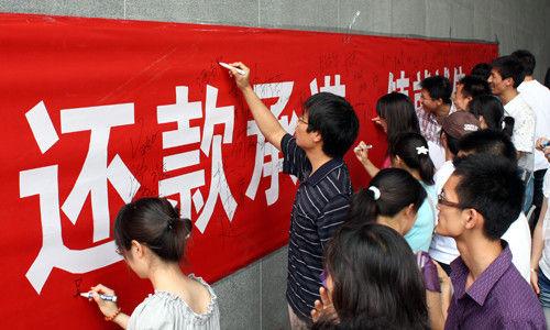 申请助学贷款的学生们在横幅上签字保证还款