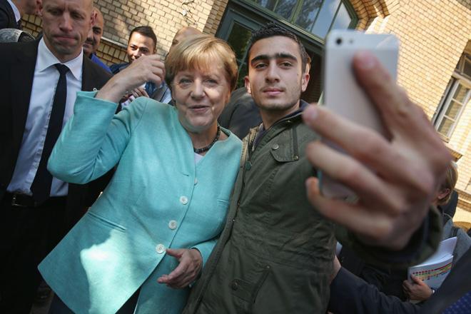 来到德国的叙利亚难民,手持iphone与德国总理默克尔自拍合影