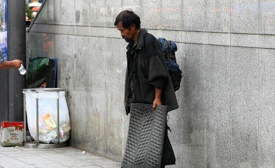 穿着一身破旧衣服,头发蓬松而油腻,手里还拎着一个脏兮兮的大袋子,流浪汉的形象常常很邋遢