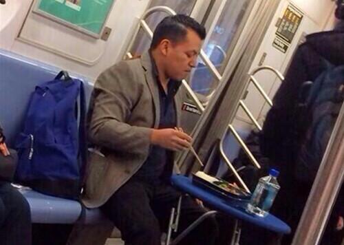 纽约地铁上,有乘客支好桌子慢慢吃晚餐