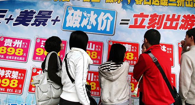 贴着大量低价游广告的牌子吸引了人们的关注