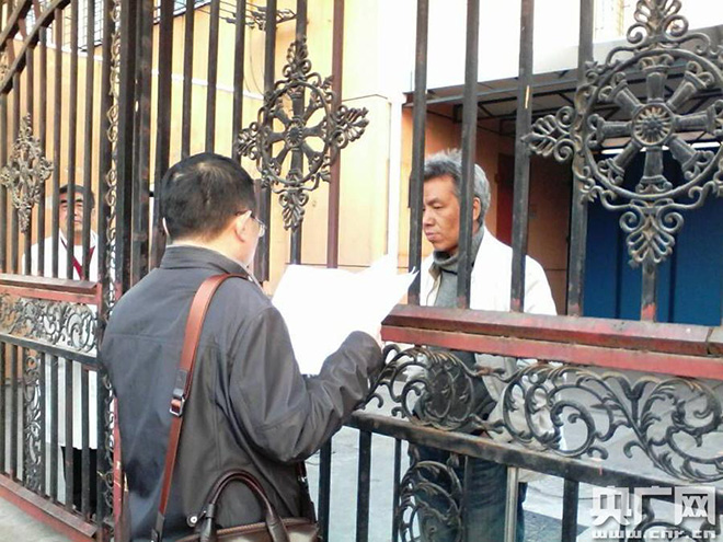杨卫华律师隔着康复院的铁栏栅给徐为送判决书(图片来源:央广网)