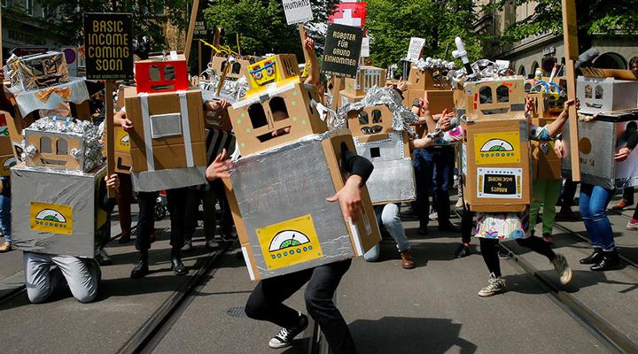 """支持""""基本收入""""政策的瑞士人打扮成机器人游行,警示机器会让人类失业"""