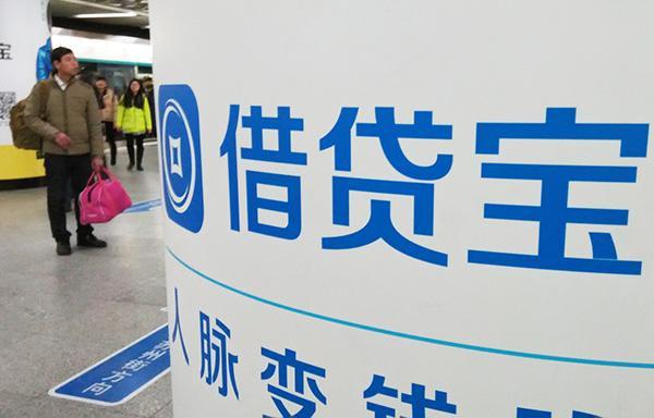 2016年1月8日,北京,一行人从借贷宝logo招牌旁经过。 图片来源:澎湃新闻