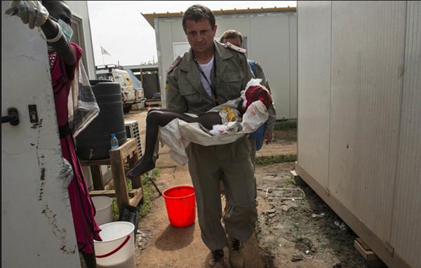 一名联合国官员抱着难民营中一名儿童的尸体,她在一场交火中丧生