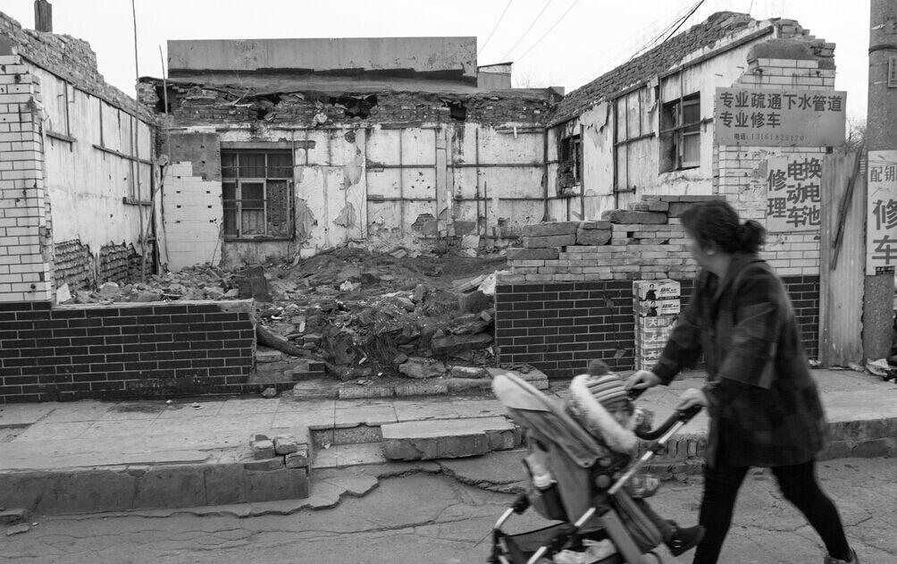 北京皇城圈西南老旧胡同,一位居民从被拆的房屋边经过。CFP供图