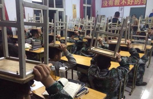 因个别学生坐姿不正,全体同学被罚顶着板凳上课。中新网图片